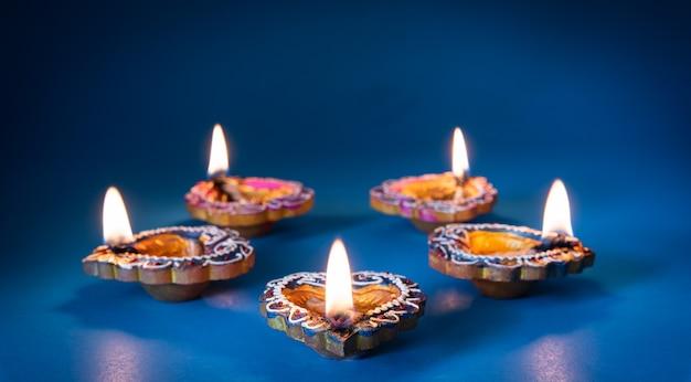 Happy diwali - lâmpadas de clay diya acesas durante o dipavali, o festival hindu de celebração das luzes