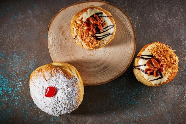 Happy hanukkah and hanukkah sameach são donuts judaicos tradicionais com caramelo, chocolate e açúcar em pó.