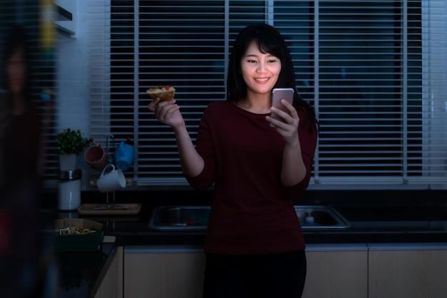 Happy hour virtual de mulher asiática, conhecer e comer pizza entrega da caixa on-line com o amigo ou tirar foto usando a câmera do telefone móvel na cozinha à noite durante a hora do isolamento em casa.