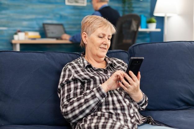 Hapy idosa mandando mensagens de texto no telefone relaxando no sofá aproveitando o estilo de vida de aposentadoria