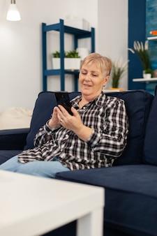 Hapy senhora idosa mensagens de texto no telefone relaxando no sofá, desfrutando de estilo de vida de aposentadoria, sobrancelhas de mulher sênior ...