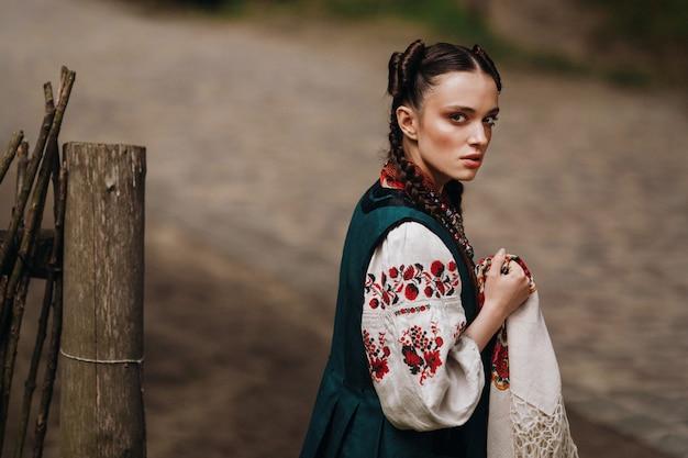 Сharming menina no vestido tradicional ucraniano está andando