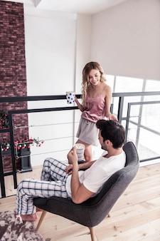 Harmonia. mulher loira magra de cabelos compridos em uma bela lingerie parecendo em paz enquanto passava a manhã com o marido em casa