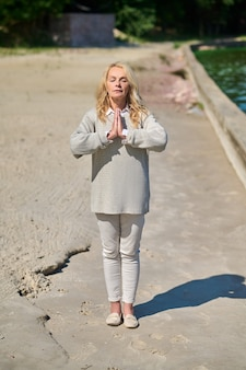 Harmonia. mulher loira muito tranquila com os olhos fechados em pose de namastê perto da água em um dia ensolarado e quente