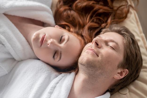 Harmonia. um homem e uma mulher de branco parecendo relaxados e em paz