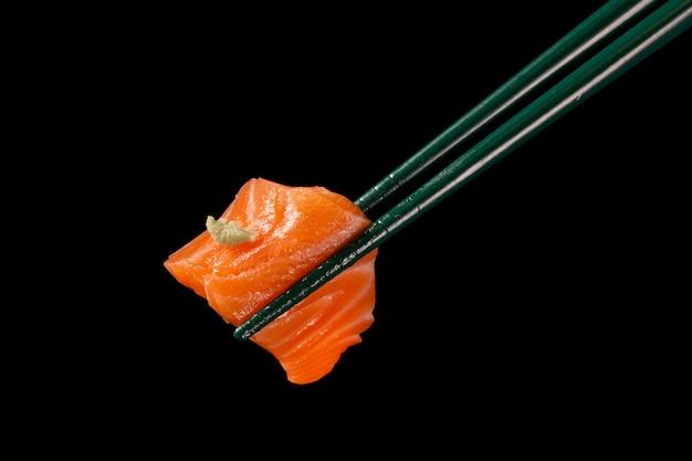 Hashi segura sushi e rolos isolados sobre fundo preto