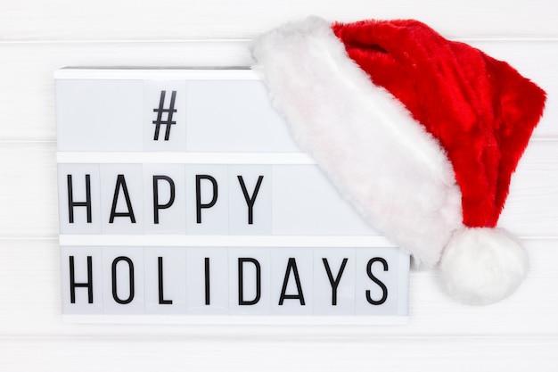Hashtag de boas festas em lightbox branco com chapéu de papai noel vermelho