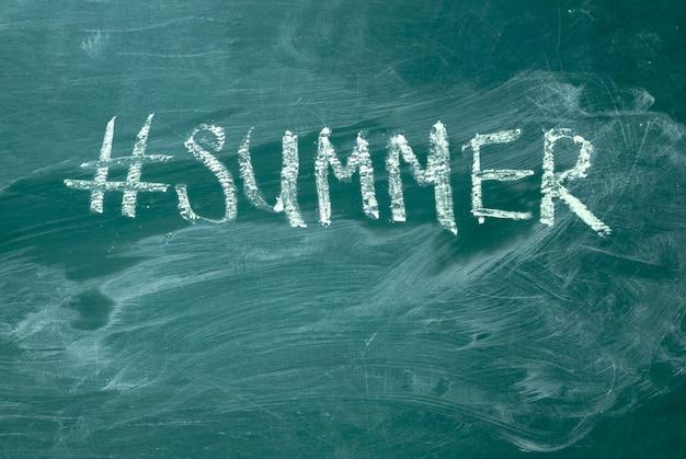 Hashtag do verão escrito à mão com giz branco em um quadro-negro verde.