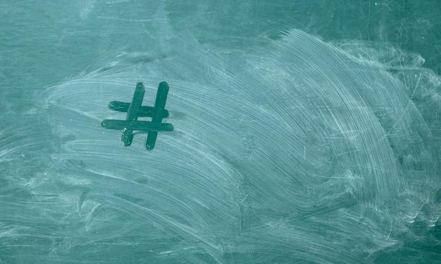 Hashtag escrito à mão com giz branco em um quadro-negro verde.