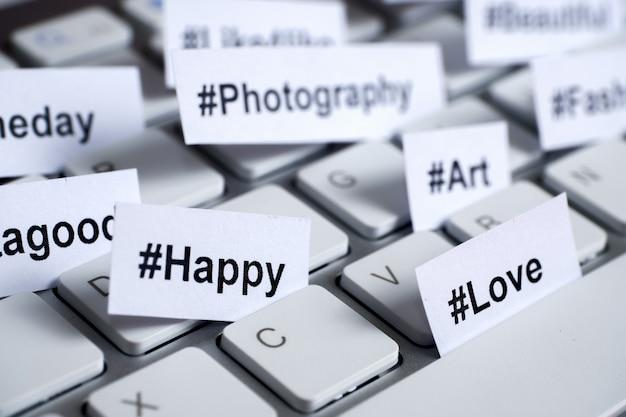 Hashtags populares impressas em papel branco inseridas no teclado.