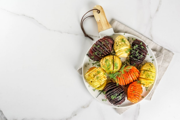 Hasselback assado beterraba, cenoura, batata, com ervas frescas