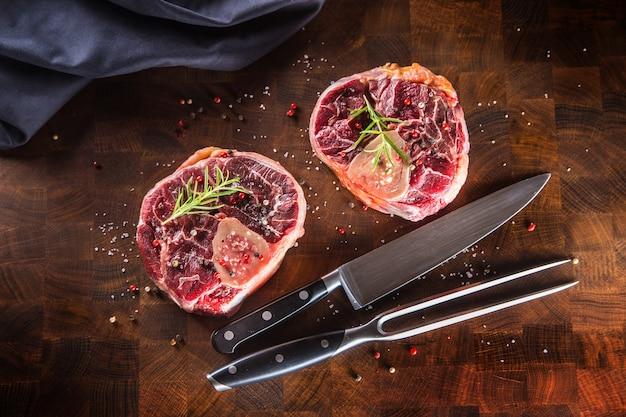Haste de carne de duas peças cruas na placa de açougueiro de madeira com garfo e faca.