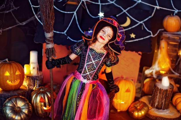 Hcute garotinha em uma fantasia de bruxa com vassoura mágica comemora em casa em um interior com abóboras e casa mágica de papelão no fundo.