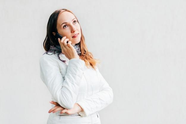 Headshot do retrato da jovem mulher que olha afastado pensativamente e que fala no telefone celular.