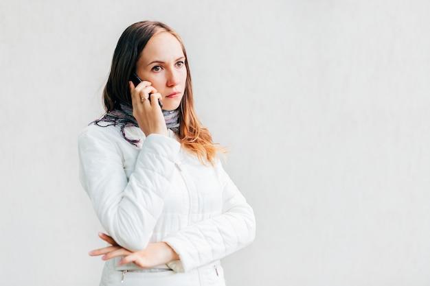 Headshot do retrato da menina virada, infeliz, séria com braços cruzados que fala no móbil.