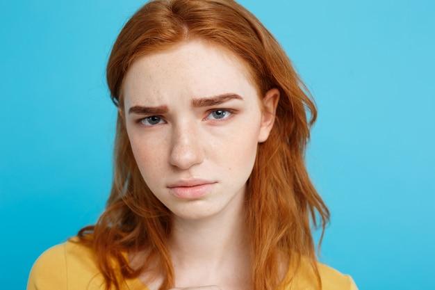 Headshot retrato de adolescente ruiva macia com expressão séria olhando a câmera. modelo de mulher caucasiana com cabelo de gengibre posando no interior de um fundo azul. espaço de cópia.