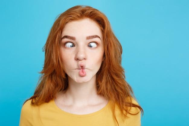Headshot retrato de feliz gengibre menina cabelo vermelho com cara engraçada olhando câmera. fundo azul pastel. espaço de cópia.