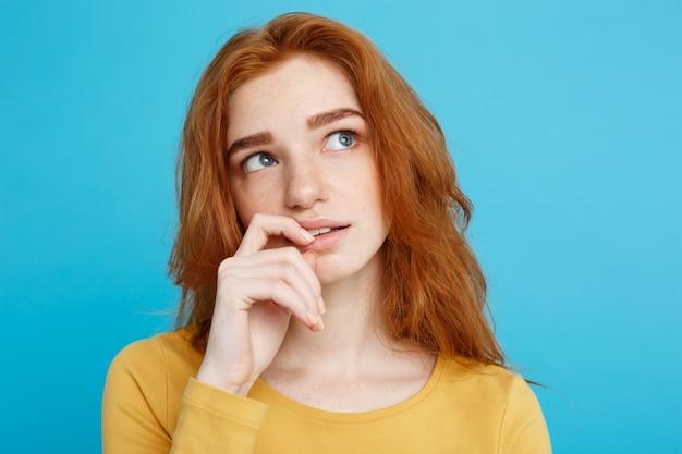 Headshot retrato de feliz gengibre menina de cabelo vermelho com sardas sorrindo olhando câmera. fundo azul pastel. espaço de cópia.