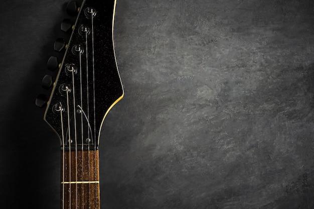 Headstock da guitarra elétrica preta no assoalho preto do cimento. vista superior e espaço da cópia para o texto. musica rock.