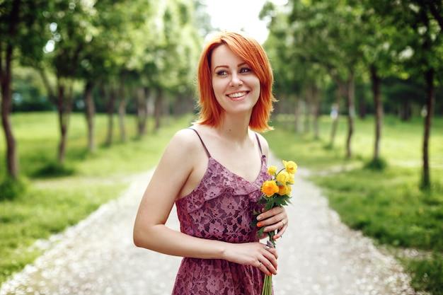 Heair vermelho mulher segurando flores da primavera