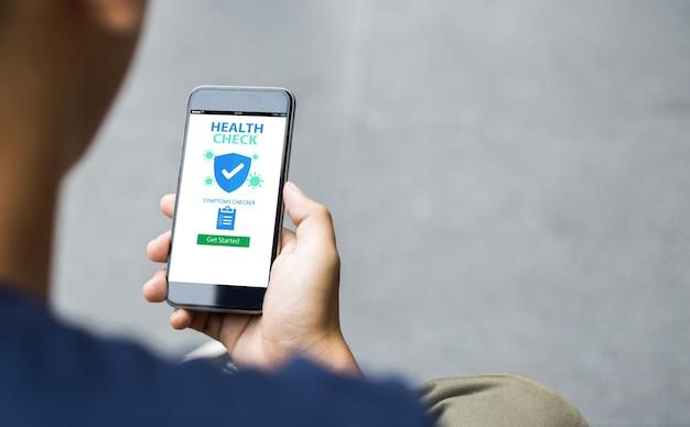 Health check covid-19 conceito de aplicativo móvel do verificador de sintomas. homem de mãos dadas com o telefone móvel