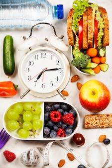 Health & fitness comida em lancheiras, medindo fita e alarme
