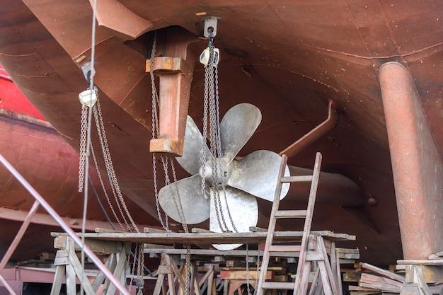 Hélice de pá fixa e leme navio de carga em terra no pátio de reparos