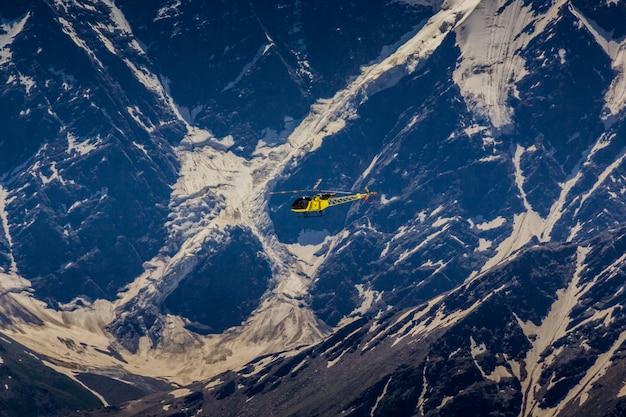 Helicóptero amarelo em um fundo de montanha