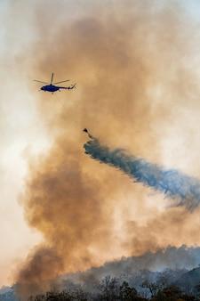 Helicóptero bombeiro despeja água em incêndio florestal