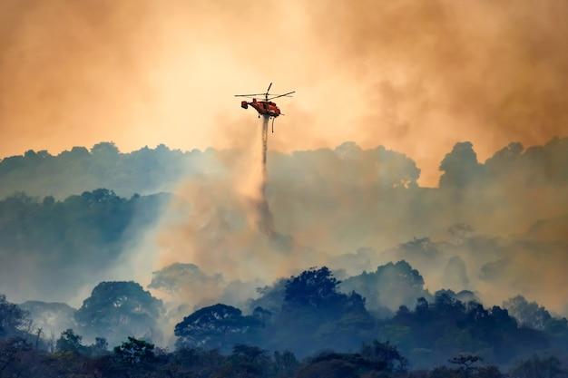 Helicóptero bombeiro lançando água em um incêndio florestal