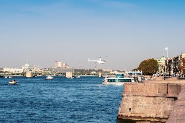 Helicóptero branco da administração da cidade sobre o rio neva, em são petersburgo.