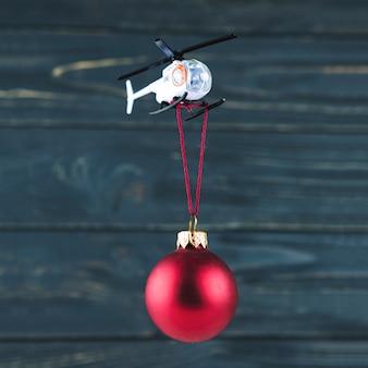 Helicóptero de brinquedo carregando enfeite de natal