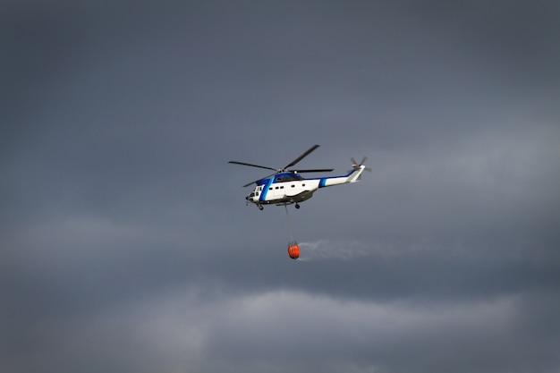 Helicóptero de combate a incêndio com cesta de bambi