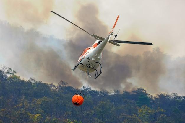 Helicóptero de combate a incêndios despeja água em incêndio florestal
