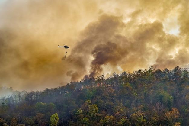 Helicóptero de combate a incêndios lançando água em um incêndio florestal