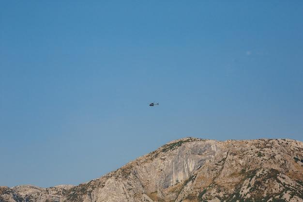 Helicóptero de passageiros voa no céu azul sobre as montanhas
