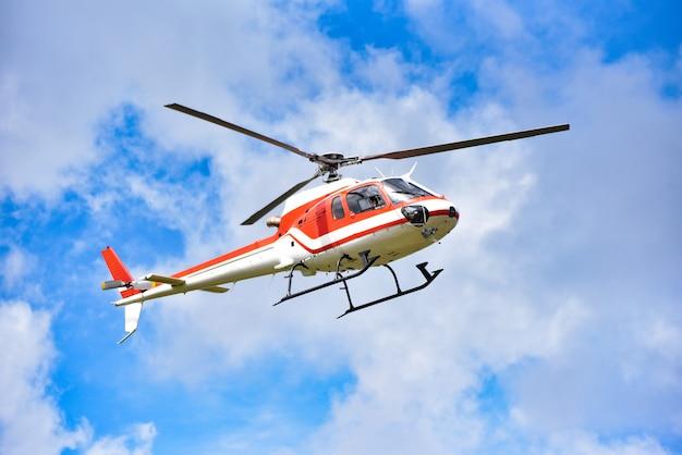Helicóptero de resgate de helicóptero voando no céu / branco vermelho voar de helicóptero no céu azul com nuvens bom dia de ar brilhante