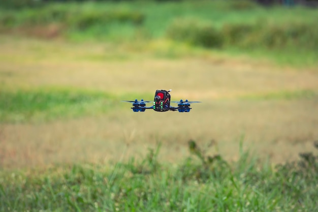 Helicóptero drone voando rápido com câmera digital em campo verde