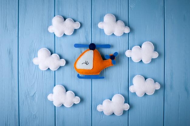 Helicóptero e nuvens alaranjados do ofício no fundo de madeira azul com copyspace. senti brinquedos artesanais.