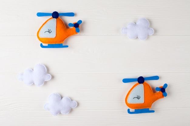 Helicóptero e nuvens alaranjados do ofício no fundo de madeira branco com copyspace. senti brinquedos artesanais.