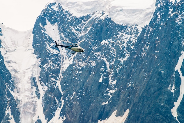 Helicóptero no ar contra a cena da montanha de neve