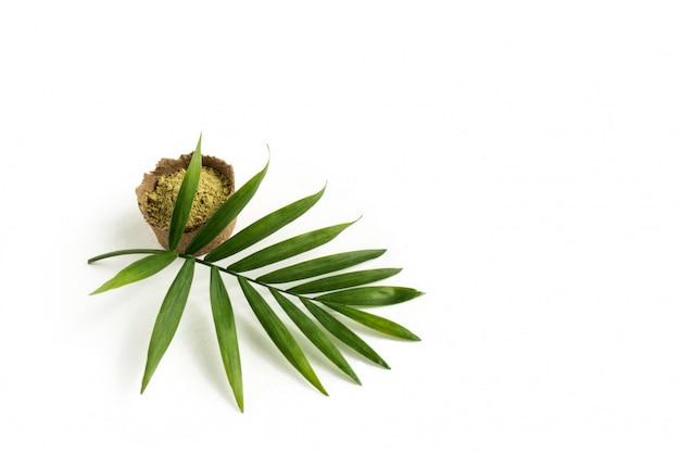 Henna em pó para tingir cabelos e sobrancelhas e desenhar nas mãos, com folha de palmeira verde