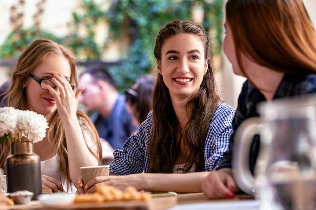Henparty com melhores amigas e lanches deliciosos no acolhedor café ao ar livre em um dia quente de verão
