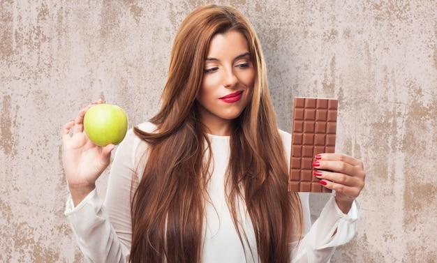 Hesitando mulher com maçã e chocolate