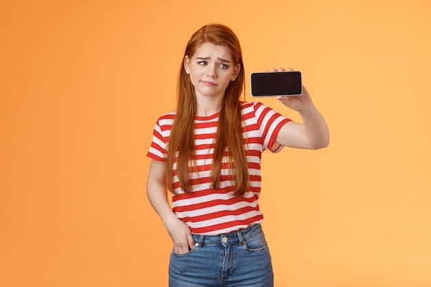 Hesitante decepcionada mulher ruiva fofa sorrindo descontente segurar smartphone horizontal olhar dispositivo para cima ...