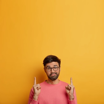 Hesitante e surpreso, o homem aponta para cima com expressão confusa, aponta para o espaço em branco, tem dúvidas e pede sua opinião, faz uma escolha perplexa, usa óculos e macacão casual parede amarela