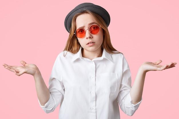 Hesitante mulher bonita e hippie encolhe os ombros em perplexidade, sendo incerta e tem expressão sem noção, usa chapéu estiloso e óculos de sol vermelhos, posa contra a parede rosa quem se importa?