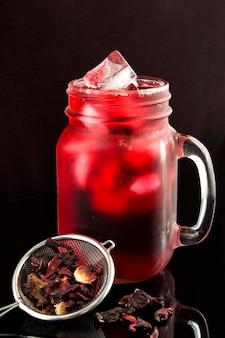 Hibisco gelado ou chá de karkade no copo sobre fundo preto. close-up.