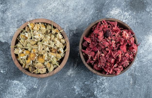 Hibisco seco e chá de camomila em tigelas de madeira.