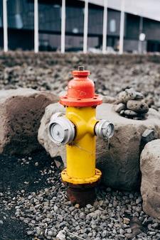 Hidrante amarelo com tampa vermelha e tampas prateadas